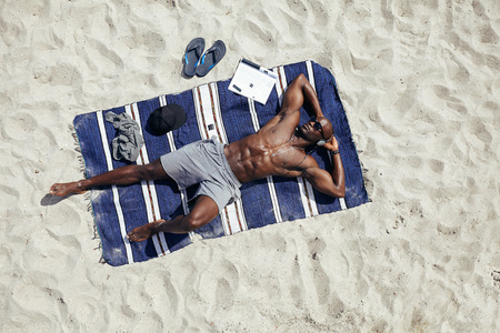 beach mat: Directly above shot of  muscular young african guy sunbathing on beach. Man wearing sunglasses listening to music on while lying on a beach mat outdoors.
