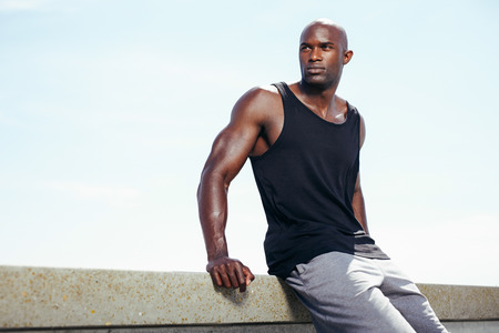 Image of muscular young man sitting outdoors against sky looking away at copyspace. Fit african male model.  Imagens