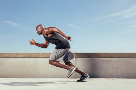 corriendo: El hombre comienza a correr en el camino con el cielo azul en el fondo y copia espacio a su alrededor. El desenfoque de movimiento. Foto de archivo