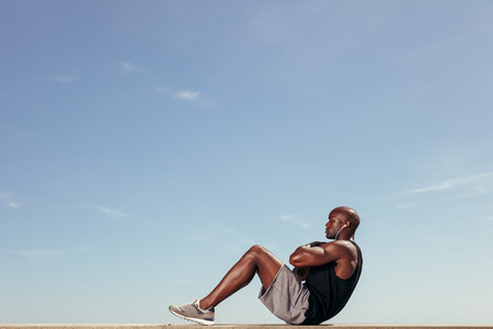 Side view of fitness model doing crunches against blue sky. Young african man doing abdominal exercise outdoors. 免版税图像