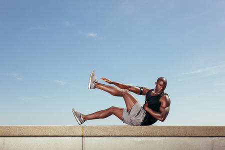Fit young guy doing stretching workout outdoors. Muscular young fitness model exercising against sky. Standard-Bild