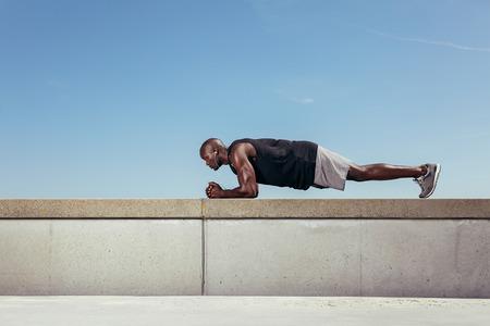 nucleo: Vista lateral de una fuerte atleta africano joven que hace ejercicio básico en una pared por una pasarela. Atleta joven muscular ejercicio al aire libre contra el cielo claro. Con una gran cantidad de espacio de copia.