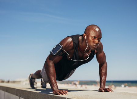 Young athletic man doing push-ups. Fitness model doing outdoor workout. Muscular and strong guy exercising.  Stock Photo