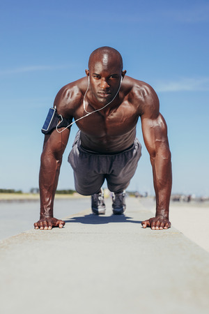 Image of shirtless young man doing push-ups. Muscular young fitness model exercising. African male model workout outdoors. Stock Photo