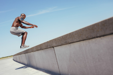 Shirtless african athlete working out on cross fit jump box outside on a wall. Muscular man doing box jumps outdoors.