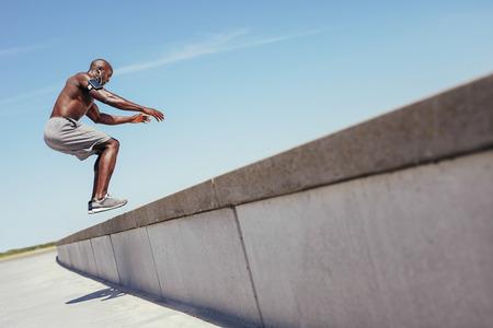 Shirtless Afrikaanse atleet uit te werken op cross fit sprong doos buiten op een muur. Gespierde man doet doos springt buiten. Stockfoto