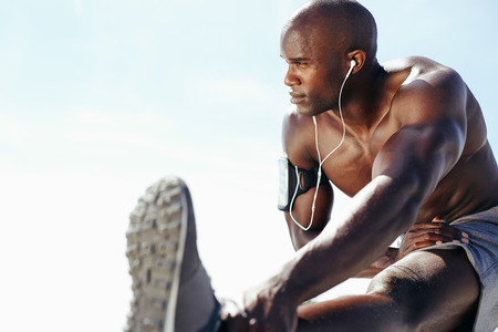 exercises: Image of muscular young man working out against sky. African man looking away with stretching his leg. Shirtless male model exercising outdoors.