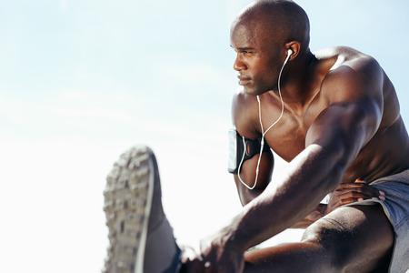 fitness hombres: Imagen del hombre joven muscular que se resuelve contra el cielo. Hombre africano que mira lejos con estirar la pierna. Modelo masculino descamisado ejercicio al aire libre. Foto de archivo