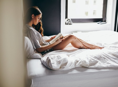 view of a comfortable bedroom: Side view of young woman sitting on her bed reading a book at home in bedroom