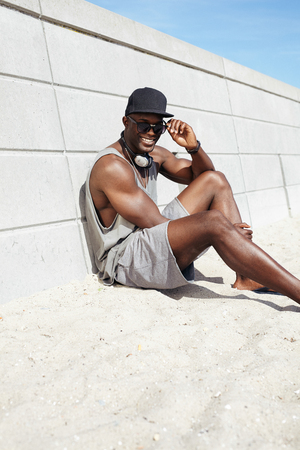beach hunk: Happy young man with headphones and sunglasses sitting on beach next to a wall. Afro american male model smiling at camera. Cheerful young guy outdoors.
