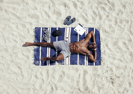 beach mat: Top view of afro american young man relaxing on beach. Muscular guy wearing sunglasses and listening to music on headphones lying on a beach mat. Shirtless male model sunbathing. Stock Photo