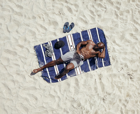 above head: Top view of young guy lying shirtless on a mat reading a magazine. African male model relaxing on beach.