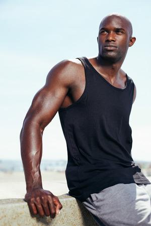 modelos hombres: Retrato del modelo masculino africano joven hermoso que miraba lejos. Muscular joven al aire libre.