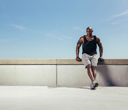 Image of fit young man relaxing on embankment after his run against blue sky. African male athlete outdoors with copyspace.