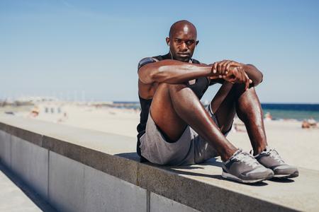 deportista: Retrato de joven atleta en forma de relax en malecón mirando a la cámara. Hombre africano muscular en reposo después de su entrenamiento.