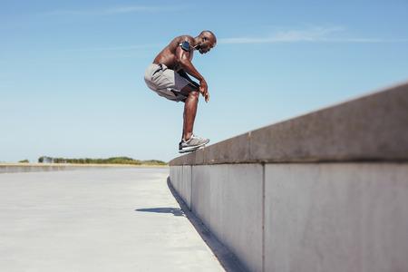 cuerpo hombre: Imagen de atleta joven sin camisa saltando de una pared. Modelo masculino de la aptitud africana que hace ejercicio de salto al aire libre.