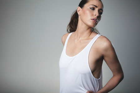tank top: Pretty young female model posing tank top. Young brunette looking away on grey background with copy space.