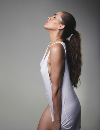 one eye closed: Side view of young brunette wearing a tank top standing with her eyes closed. Sensual female model on grey background.