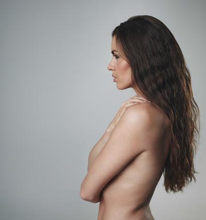 Вид сбоку без рубашки женщина с красивыми вьющимися длинными волосами. Сексуальная женщина модель на сером фоне