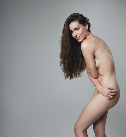 Beautiful nude woman posing on grey background. Caucasian naked female model looking happy.