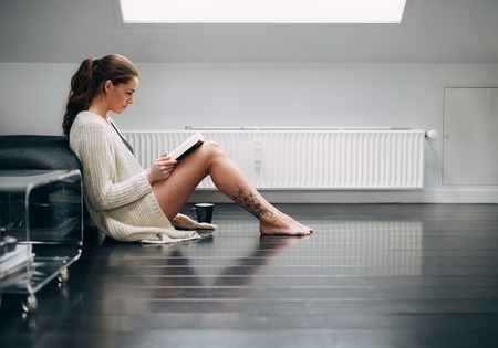 copy room: Side view of attractive young woman sitting on floor reading book. Caucasian female model at home reading a novel.