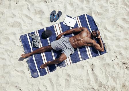 해변에서 일광욕 근육 질의 젊은 남자의 상위 뷰. 선글라스를 착용하고 헤드폰 매트에 누워 헤드폰에서 음악을 듣고 아프리카 남자 스톡 콘텐츠