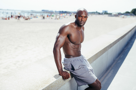 shirtless man: Portrait of muscular young african man sitting on a beach embankment looking at camera. Shirtless young man sitting on at promenade. Stock Photo