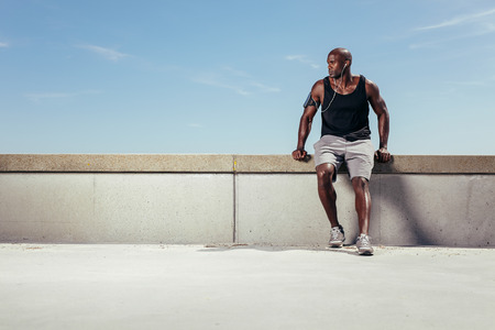 Muscular young man relaxing on embankment looking away copyspace. African male athlete wearing earphones outdoors. Male runner relaxing. photo