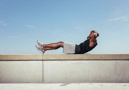 Athlete doing sit-ups against sky. African male model exercising outdoors with copy space. Stock Photo - 31536467