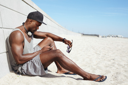 stylish man: Young guy sending a text message at the beach. African man sitting on beach using mobile phone. Muscular male model outdoors.
