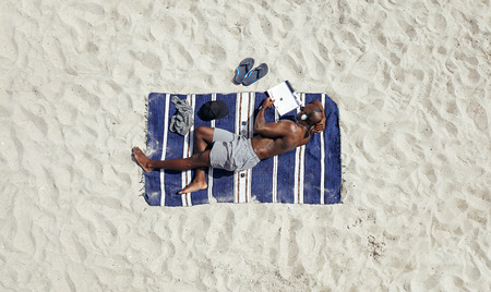 directly above: Shirtless young african man lying on a mat reading a book on a sunny day. Young guy relaxing on beach reading and listening to music on headphones.