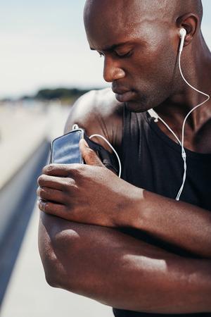 Afrikaanse gespierde atleet luisteren naar muziek. Mannelijk model luisteren naar muziek van zijn mobiele telefoon op de armband.