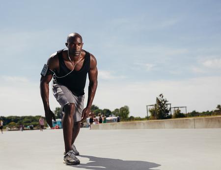 アスリート: フィットの若い男の彼のマークに実行を開始します。決定された屋外の運動選手。筋肉アフリカの男性モデル暑い夏の日に彼の実行の準備ができて。