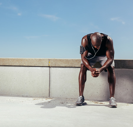 Tired young runner leaning over to catch his breath. African man sitting on a wall relaxing after fitness workout outdoors.