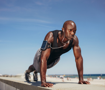 Muscular man doing push ups against blue sky. Strong male athlete working out outdoors.  스톡 콘텐츠