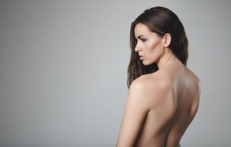 topless: Femme aux seins nus sur fond gris. Modèle féminin nu avec une expression vide.
