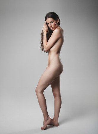 Full length portrait of naked young woman looking at camera. Caucasian female model posing nude on grey background. Stock Photo