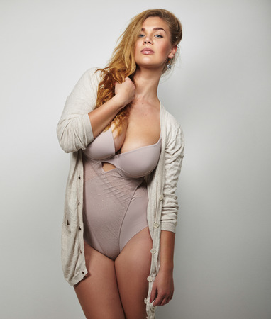 Overweight woman in underwear posing confidently against grey background. Plus size model in body stocking looking at camera. photo