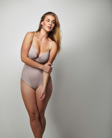 Curvaceous young lady wearing body stocking standing on grey background. Pretty young woman in lingerie looking away at copy space. Plus size female model in underwear.