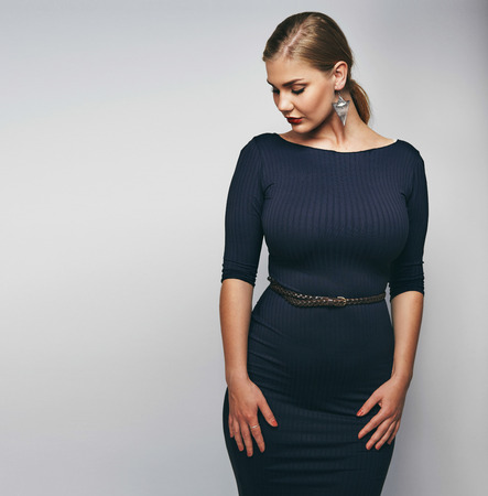 woman nude standing: Studio image of elegant young lady in black dress. Oversized and curvy female model on grey background.