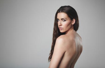 modelos desnudas: Modelo de mujer desnuda posando sobre fondo gris. Topless mujer cauc�sica mirando.
