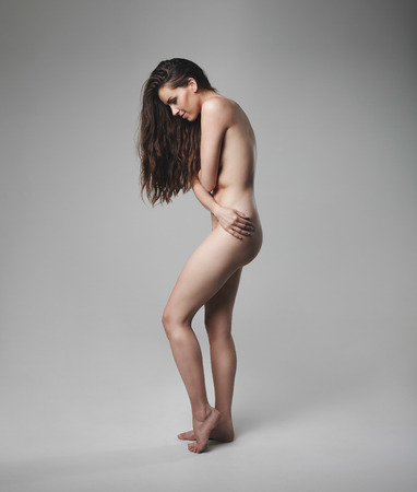 woman nude standing: Full length image of natural female standing naked on grey background. Nude brunette woman covering her breast.
