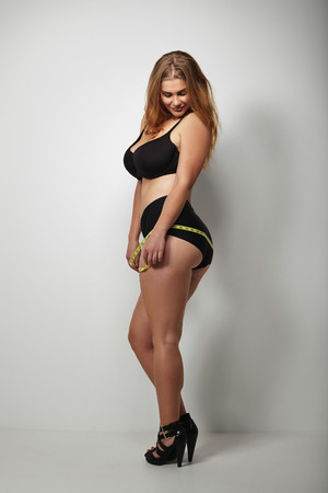 from side: Full length image of sensual young woman in bikini with tape measure around her hips looking down. Voluptuous female model in underwear.
