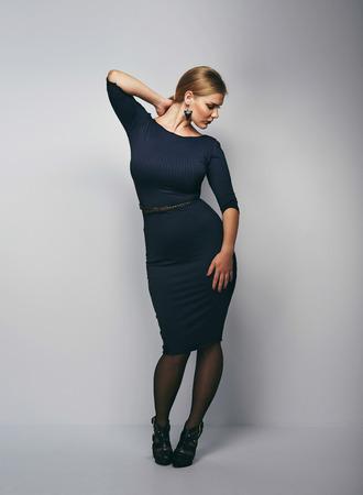 voluptuosa: Imagen de la longitud completa de la mujer magn�fica joven posando en traje negro. Elegante modelo de mujer cauc�sica sobre fondo gris. Foto de archivo