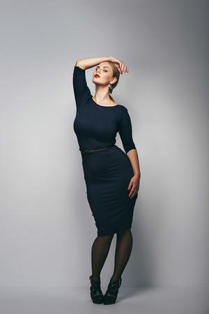 灰色の背景に黒のドレスでポーズをとってプラスのサイズの女性モデルのポートレート。曲線図と美しい女性。