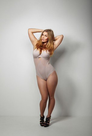 voluptuous: Full length studio image of beautiful voluptuous woman in body stockings standing on grey background. Sexy young plus size female model posing in underwear. Stock Photo