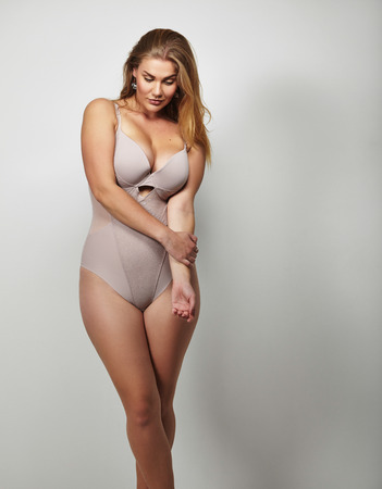 large build: Portrait of a voluptuous woman in lingerie looking down on grey background. Attractive plus size young lady in body stocking.