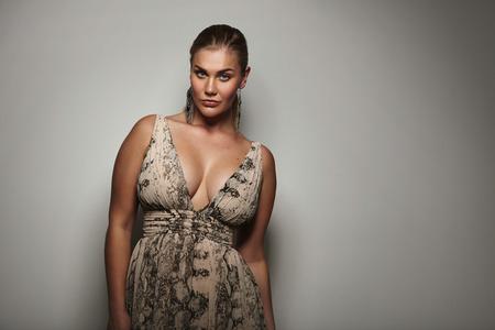 Portret van een aantrekkelijke jonge vrouw op zoek sensueel op camera. Wulpse vrouwelijke model stellen een mooie jurk tegen de grijze achtergrond met kopie ruimte.