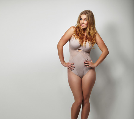 Chubby young woman in body stockings standing on grey background with her hands on hips looking at camera. Caucasian plus size female model in lingerie with copy space. Stock Photo