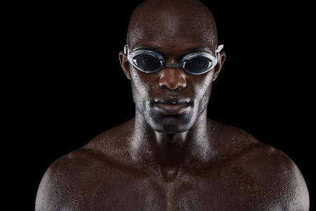 Portrait of confident male swimmer looking at camera against black background. Close-up image of muscular young man wearing swimming goggles. photo